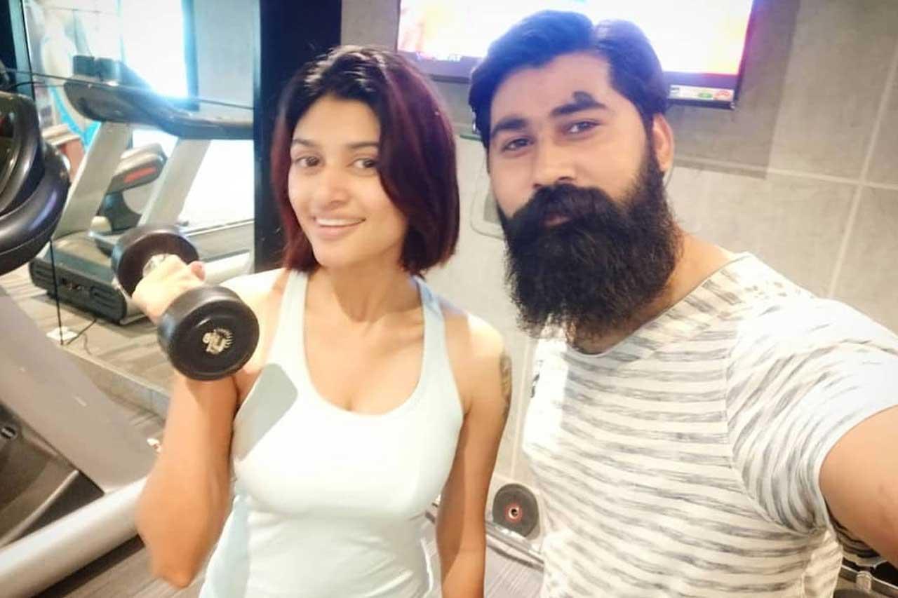 Oviya with gym trainer.